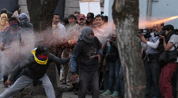 Protesters fire a rocket against the police during a confrontation near the government palace in Quito (AP)
