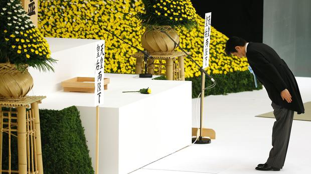 Shinzo Abe offers prayers for the war dead during a memorial service at Nippon Budokan martial arts hall in Tokyo (AP)