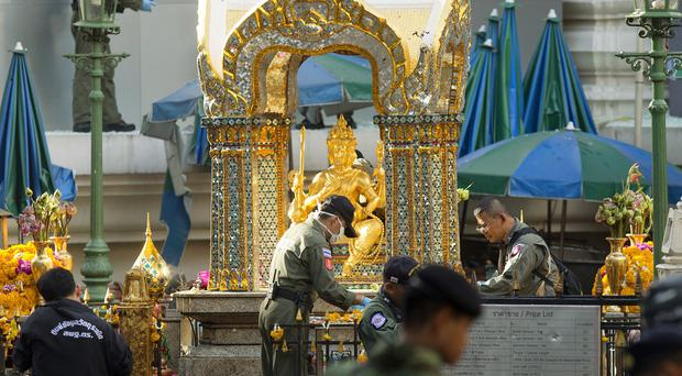 Police investigators work at the Erawan Shrine the morning after the explosion in central Bangkok (AP)