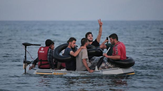 Migrants who tried to cross to the Greek island of Kos from near Bodrum, Turkey, wave as they approach the shore after their failed attempt (AP)