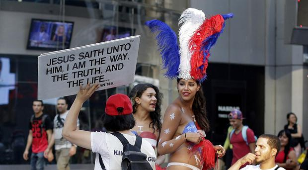 Women clad in thongs and body paint pose for photos in Times Square, in New York (AP)