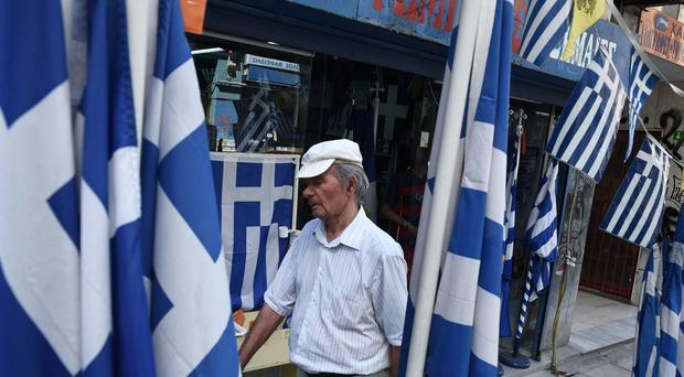 A man walks past Greek flags for sale outside a shop in the northern port city of Thessaloniki (AP)