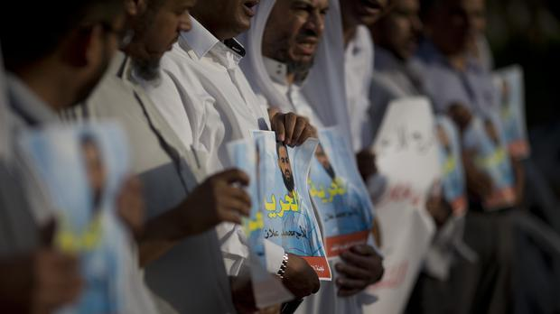 Supporters of Mohammed Allan, a Palestinian prisoner on a hunger strike, hold a photograph of him (AP)