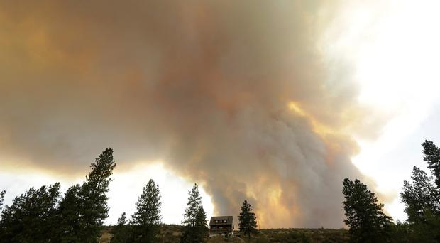 Smoke from an approaching wildfire looms over a home near Twisp, in Washington state (AP)