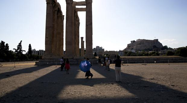 A woman carries a parasol for the strong afternoon sun as a group of tourists walk around the ruined ancient temple of Olympian Zeus, with the Acropolis hill in the background in central Athens (AP)