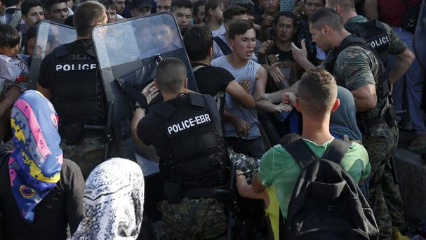 Police confront migrants at the railway station in the southern Macedonian town of Gevgelija. (AP)