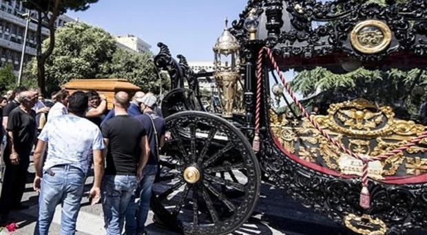 Pallbearers carry the coffin of Vittorio Casamonica next to a horse-drawn carriage in Rome (Massimo Percossi/ANSA via AP)