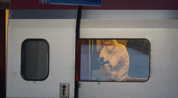 A police officer videos the crime scene inside the Thalys train at Arras railway station (AP)