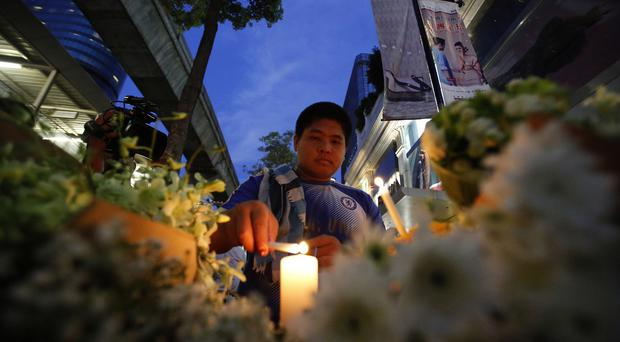 People light candles near the Erawan Shrine in Bangkok (AP)