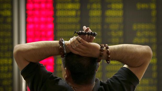 A Chinese investor monitors stock prices at a brokerage house in Beijing (AP)