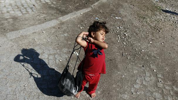 A migrant girl carries her bag at a migrant processing centre in the southern Serbian town of Presevo. (AP)