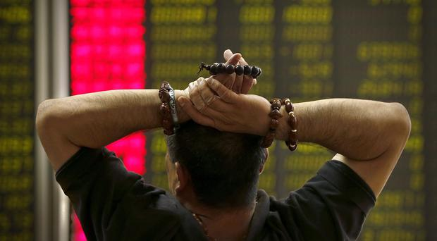 A Chinese investor monitors stock prices at a brokerage house in Beijing as stocks tumble