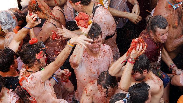 Crowds of people throw tomatoes at each other during the annual Tomatina in Bunol, Spain. (AP)