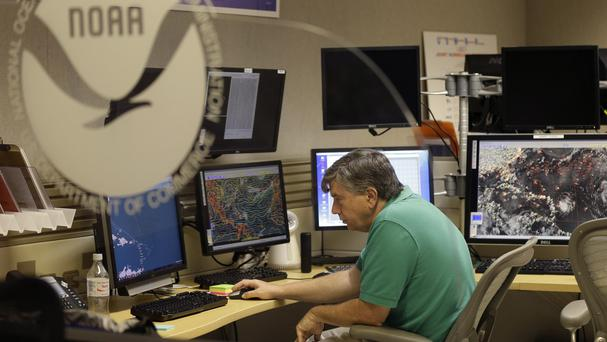 A hurricane specialist tracks the movement of Tropical Storm Erika