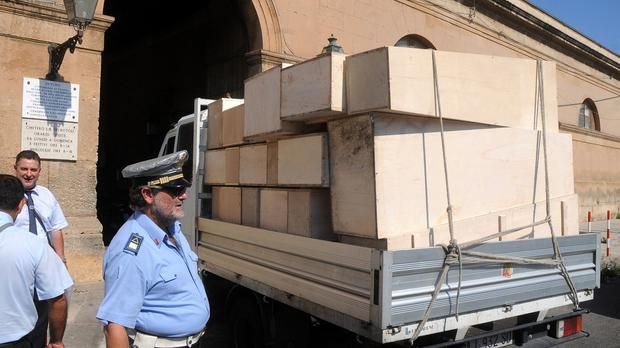 A truck carrying empty coffins arrives at a cemetery in Palermo, Italy. (AP)