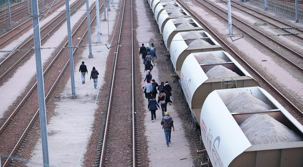 Migrants make their way along tracks near the Eurotunnel site at Coquelles in Calais