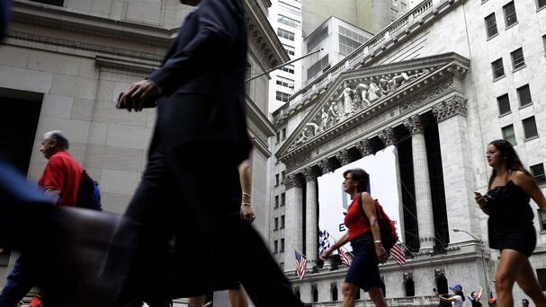 Pedestrians walk past the New York Stock Exchange at the end of a difficult month for US investors (AP)