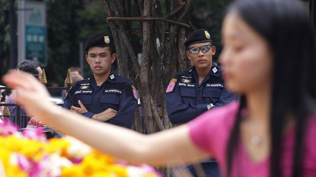 Security officers stand watch as a visitor makes an offering at the Erawan Shrine in Bangkok, Thailand (AP)