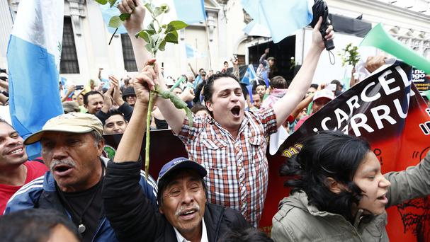 Demonstrators react in jubilation as they hear that Congress has voted to withdraw President Otto Perez Molina's immunity from prosecution (AP)