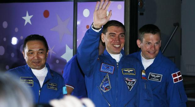 Aydyn Aimbetov, Sergei Volkov and Andreas Mogensen wave to their relatives before the launch in Kazakhstan (AP)