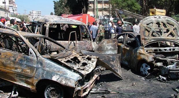Residents and emergency personnel gather at the site of a car bombing in the port city of Latakia, Syria (SANA via AP)