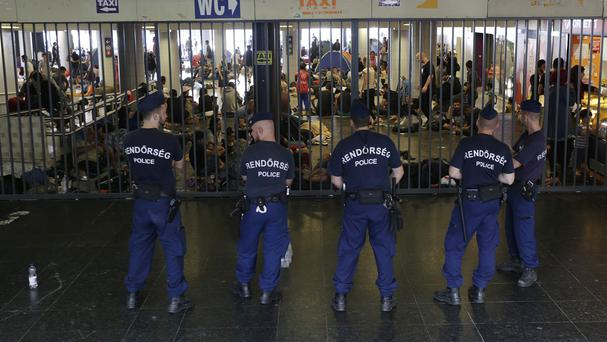 Hungarian policemen guard an entrance to the Keleti Railway Station in Budapest (AP)