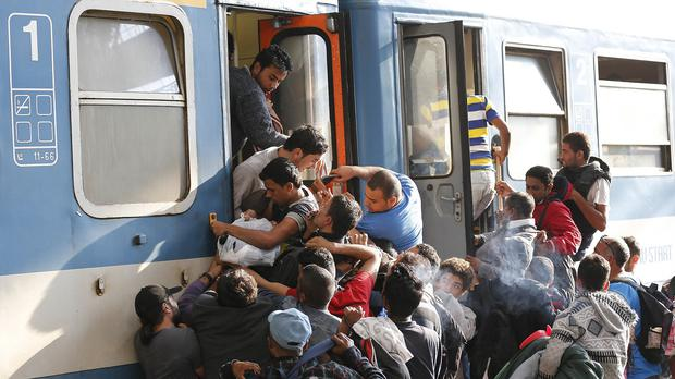 Migrants struggle to board a train at the railway station in Budapest (AP)