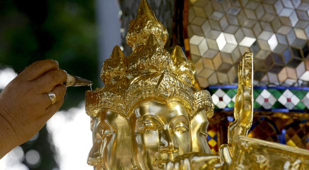 A Brahmin priest anoints Phra Phrom, the Thai interpretation of the Hindu god Brahma, with holy water (AP)