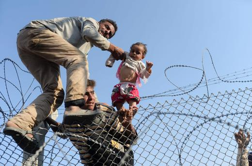 A Syrian child fleeing the war is lifted over border fences to enter Turkish territory illegally, near the Turkish border crossing at Akcakale