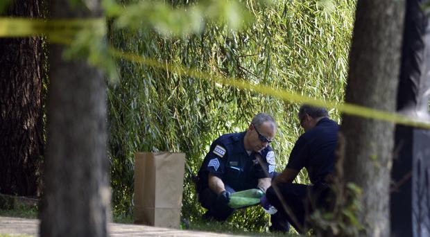 Chicago police investigators collect evidence while searching in Garfield Park (AP)