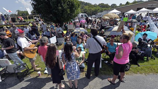 Musicians lead protesters in hymns outside the Carter County detention centre in Grayson (AP)