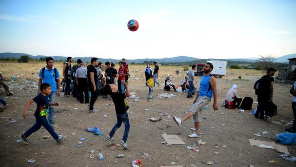 A man and children play with a ball at a refugee camp in the southern Macedonian town of Gevgelija (AP)
