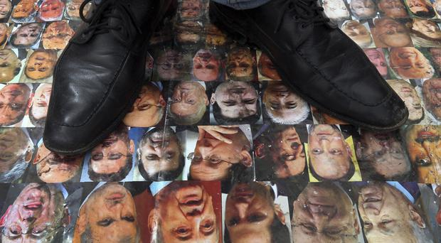 A Lebanese protester stands on a poster with the pictures of 128 Lebanese politicians. (AP)