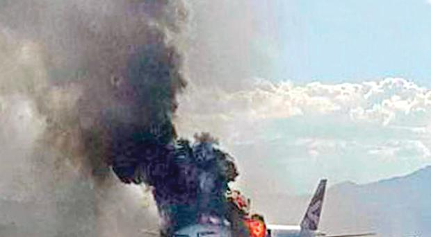 The Boeing 777-200 BA jet in flames on the runway at McCarran International Airport in Las Vegas. The 159 passengers and 13 crew on board were able to escape via the plane's emergency slides