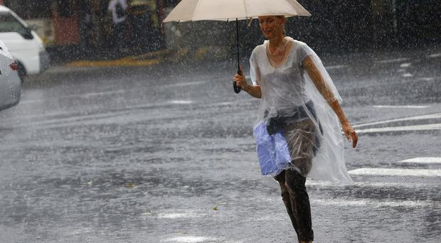 A woman holding an umbrella crosses a street in heavy rain in Tokyo's Ginza shopping district (AP)