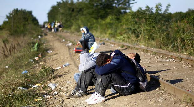 Migrants rest by the railway track near Roszke, southern Hungary (AP)