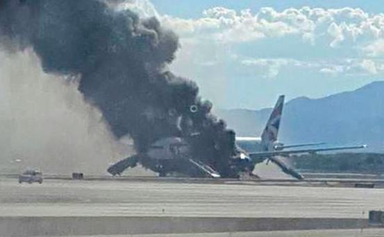 Thick black smoke belches from the Boeing 777-200 after it burst into flames at McCarran International Airport in Las Vegas