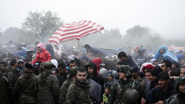 Refugees and migrants wait to pass from the northern Greek village of Idomeni to southern Macedonia (AP)