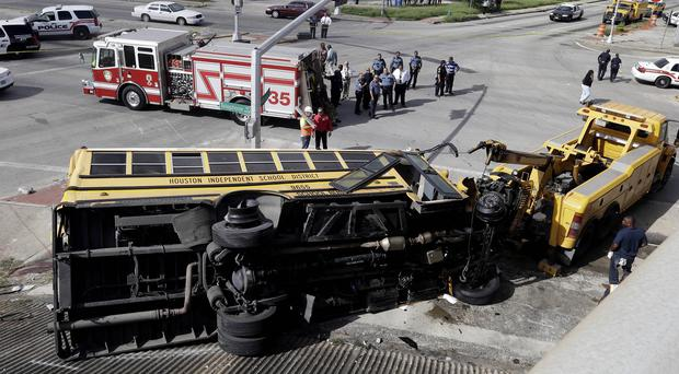 An overturned Houston school bus is prepared for towing after it drove off a highway overpass. (AP)