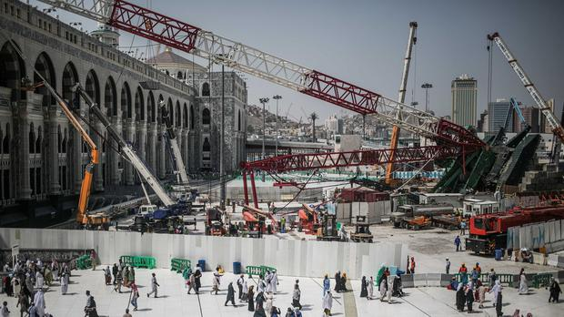 Muslim Pilgrims walk past the site of the crane collapse that killed more than 100 at the Grand Mosque in Mecca (AP)