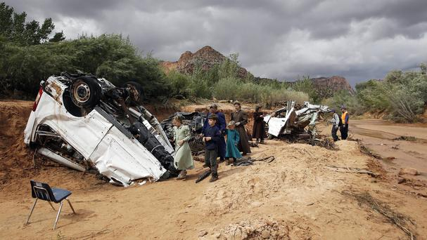 People walk pass damaged vehicles swept away during a flash flood in Hildale (AP)