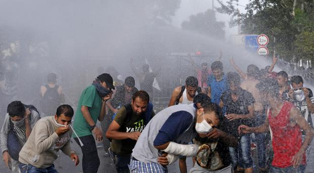 Hungarian police spray water on refugees at the