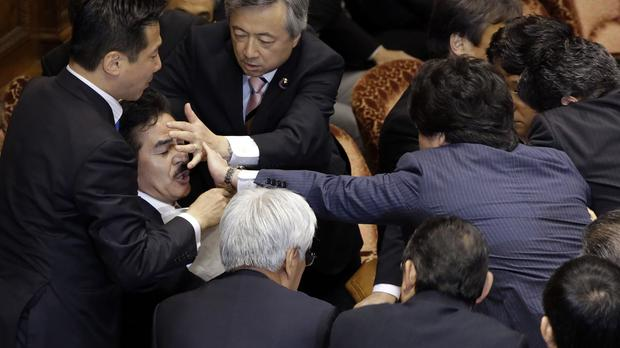 Ruling party MP Masahisa Sato, second left, is prevented from reading documents by opposition members. (AP)