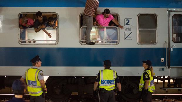 Refugees look out of a train stopped and checked by Slovenian border police, at the railway station in Dobova (AP)