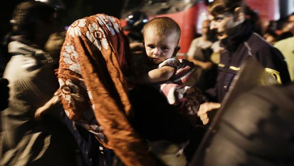 A woman holding a crying baby is pulled out of the crowd of refugees at the border checkpoint in Obretzje, Slovenia (AP)