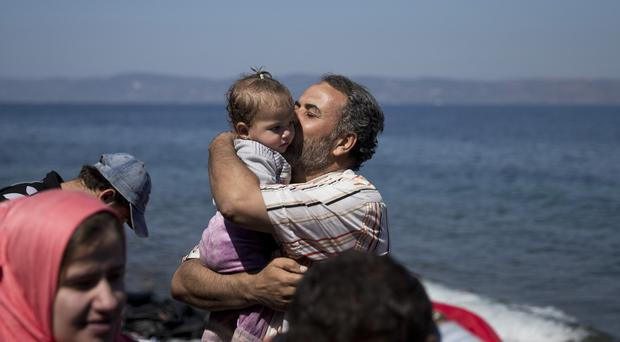A Syrian man kisses his daughter after they arrived aboard a dinghy from Turkey, to the island of Lesbos