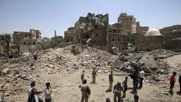 Civilians and security forces gather near a house damaged in a Saudi-led airstrike in Yemen