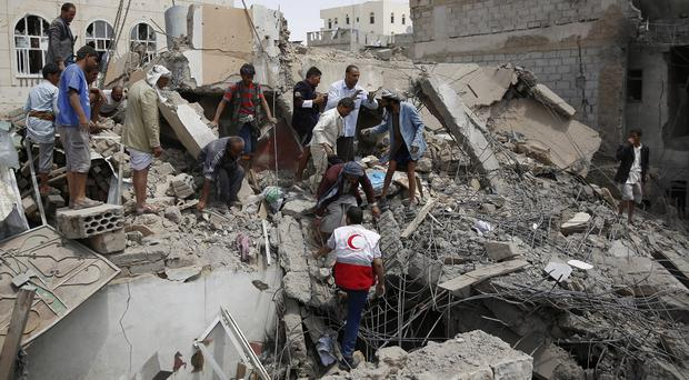Rescue workers search for survivors after an air strike in Sanaa. (AP)