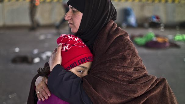 A Syrian refugee is comforted by her mother after spending the night at a collection point on the Austrian side of the Hungarian-Austrian border near Nickelsdorf. (AP)
