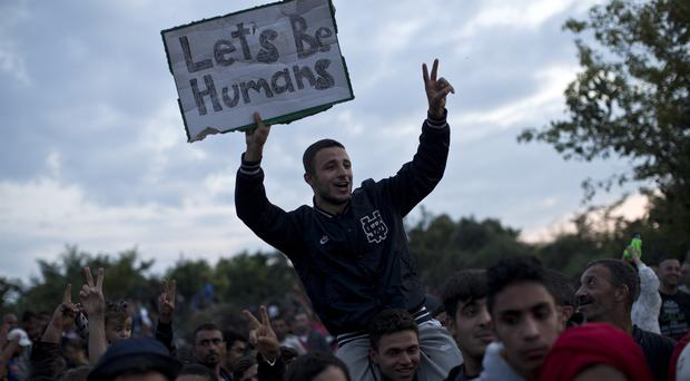 A man holds a poignant sign as he waits with other migrants and refugees to be boarded on to buses in the town of Babska, Croatia, close to the border with Serbia (AP)